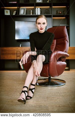 Portrait of a stunning fashionable woman sitting in a luxurious leather chair. Business, elegant businesswoman. Modern interior, furniture.