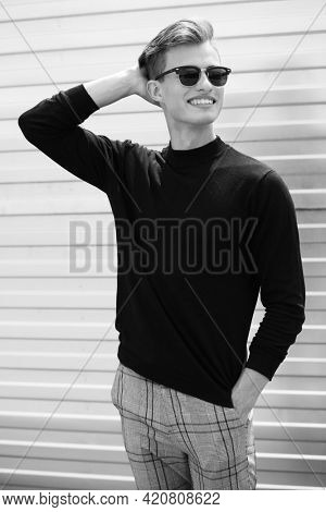 Black-and-white portrait of a handsome positive young man in black pullover and sunglasses standing outdoor and smiling. Happy people concept.