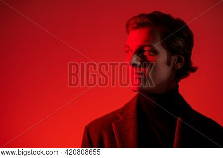 Portrait of a serious handsome man in elegant clothes posing at studio in red light. Men's beauty. Fashion. Copy space.