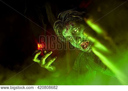 Halloween, horror movie. Close-up portrait of a scary zombie boy teenager in green light.