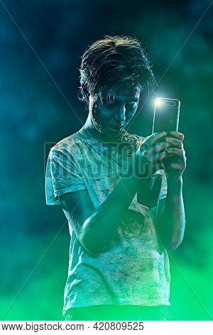 Halloween. Scary zombie boy teenager makes selfie on his smartphone.