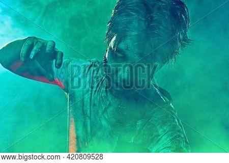 Halloween. Portrait of a scary zombie boy teenager in smoke. Horror movie.