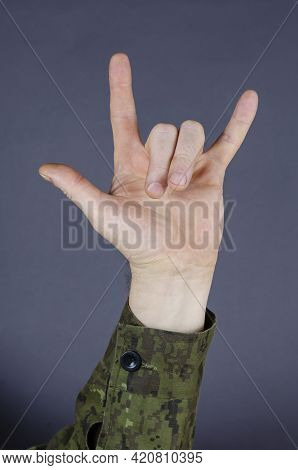Hand In Camouflage Shows Gesture With His Fingers On Gray Background. Palm Shows The Gesture Of A Go