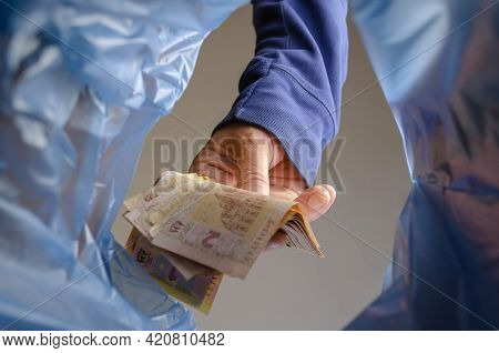 The Hand Throws Money In The Trash. A Man Is Holding Several Ukrainian Hryvnia Over The Trash Garbag