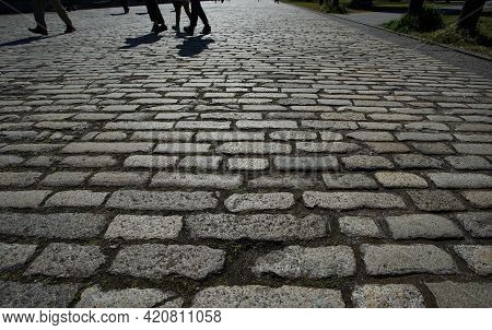 A Cobblestone Sidewalk With People On A Sunny Day