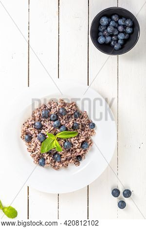 Delicious Risotto With Blueberries Served On White Wooden Table, Flat Lay