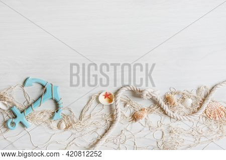 Sea Background With Fishing Net, Anchor And Seashells Top View On White Wooden Background. Summer Se