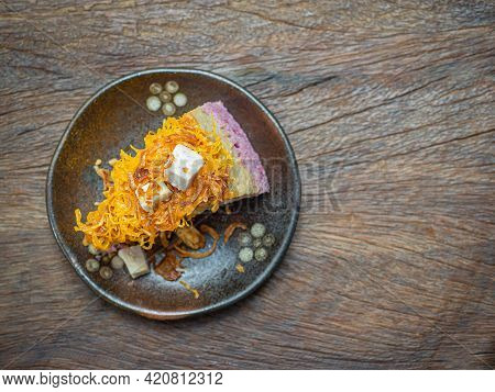 Top View Photo Of Chiffon Cake Topped With Thai Taro Custard And Foy Thong Is Placed On A Plate On A