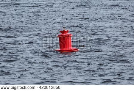 A Signal Red Buoy On Blue Water
