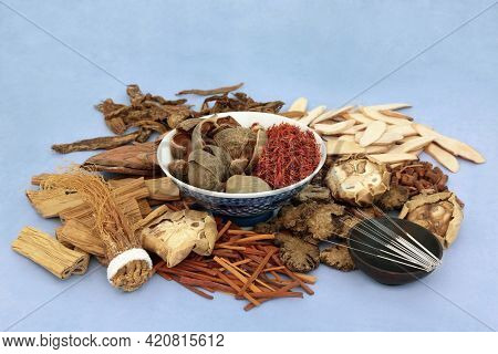 Chinese acupuncture needles with herbs and spice used in traditional herbal medicine and  treatment  on mottled blue background. Alternative and natural health care concept.