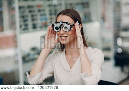 Portrait Of Happy Young Woman During Eye Exam With Test Goggles Glasses At Optometrist Optician.