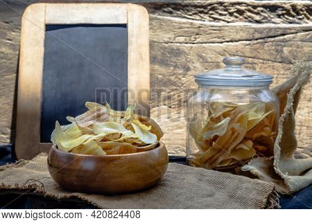 Homemade Banana Chips In Wooden Bowl And Glass Jar On Sackcloth With Vintage Style. Banana Dessert,
