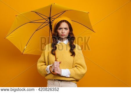 Happy young woman with long red hair wearing beret and sweater standing under umbrella over yellow background