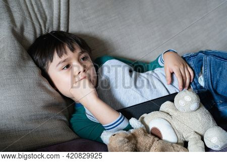 Candid Shot Of Kid Lying On Sofa Biting His Finger Nails While Watching Tv, Child Boy Bite His Nails