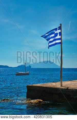 Greek flag in the blue sky on pier and traditional greek fishing boat in the Aegean sea with greek flag, Milos island, Greece