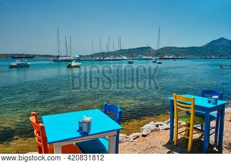Cafe restaurant table of street cafe with chairs on beach in Adamantas town on Milos island with Aegean sea with boats and yachts in background. Milos island, Greece
