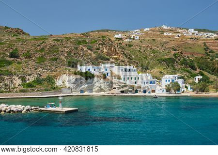 Greek fishing village with traditional whitewashed white houses on Milos island view from Aegean sea in Greece