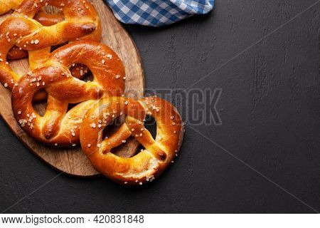 Fresh baked homemade pretzel with sea salt on stone table. Classic beer snack. Top view flat lay with copy space