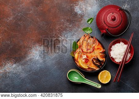 Traditional Thai soup Tom Yum kung with seafood, coconut milk and chili pepper and rice bowl. Top view flat lay with copy space