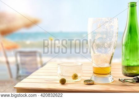 Aperitif Finished On The Beach With A Glass Of Beer And A Bowl With Almost Empty Olives