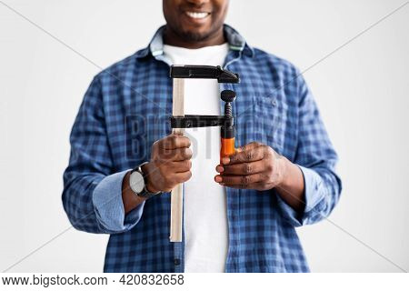 Black Male Hands Holding Construction Tool Clamp, Ready For Repairs At Home, Standing On White Wall