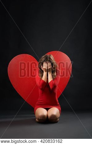 Vertical Shot Of A Heartbroken Woman Crying Sitting On The Floor Near Big Red Heart Symbol Symbolic
