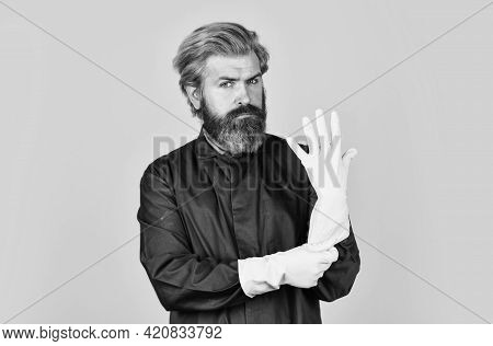 Bearded Man Wear Rubber Gloves. Mature Janitor In Uniform Yellow Background. Spring Cleaning Service