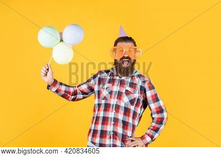 Mature Guy In Checkered Shirt With Party Balloons. Stylish Male Having Fun On Birthday. Bearded Man