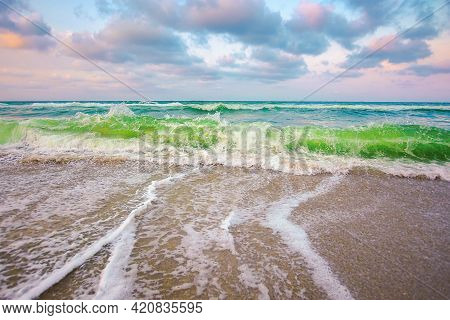 Cloudy Seascape Scenery In Evening Light. Waves Crush On The Sandy Beach. Dramatic Weather Nature Ba