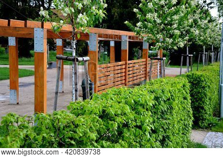 Behind A Hedge In The Park Stands A New Pergola Made Of Brown Wood By A Garden Architect. It Is Line