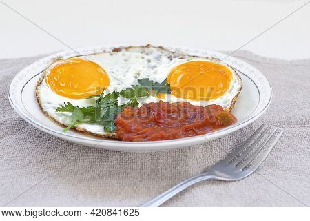 Side View Of Fried Eggs With Parsley And Seasoning Of Vegetables On A Plate Closeup. Selective Focus