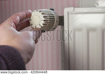 Hand Turns Off The Radiator Thermostat To A Minimum With The Arrival Of Spring And Warming In The Ap