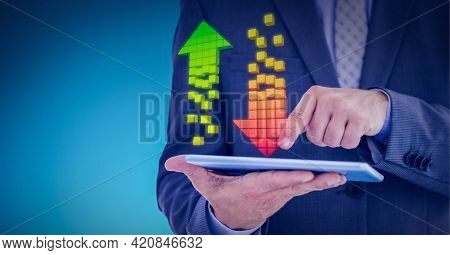 Multiple arrows over mid section of businessman holding digital tablet against blue background. computing technology concept
