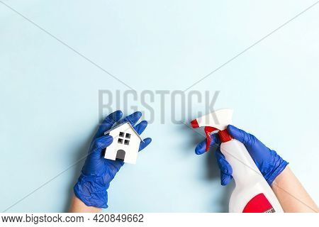 Female Hands In Rubber Gloves Disinfect A Toy House With An Alcohol Spray For Coronavirus Protection