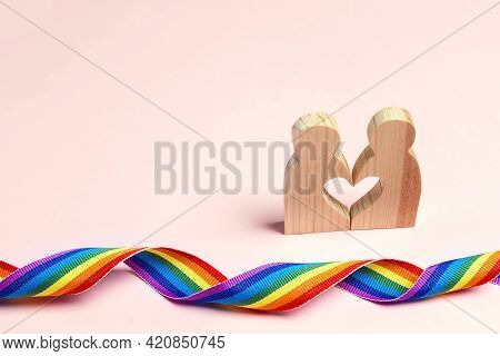 Lgbt Couple Wooden Figures With Rainbow Ribbon. Pride Tape Symbol. Gender Equality Concept.