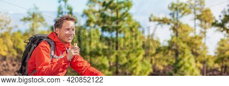 Eating granola bar snack on forest hike happy camper man hiking in nature landscape holding healthy food breakfast bar. Banner panoramic
