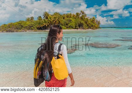 Snorkel water sport activity. Young Asian woman on snorkeling adventure travel vacation walking with mask and fins. French Polynesia Tahiti island coral reef lagoon in Pacific Ocean. Rangiroa atoll.