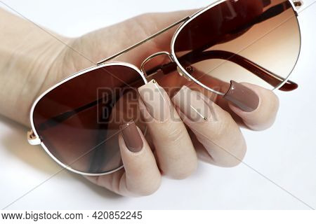 Fashionable Sun Glasses And Stylish Manicure In Beige Brown Nail Polish Colors.
