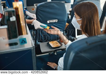 Cabin Attendant Giving Woman Pack Of Tissues And Candy Bar