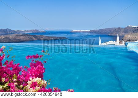 Clear Pool Water And View Of Santorini Caldera With Flowers, Greece