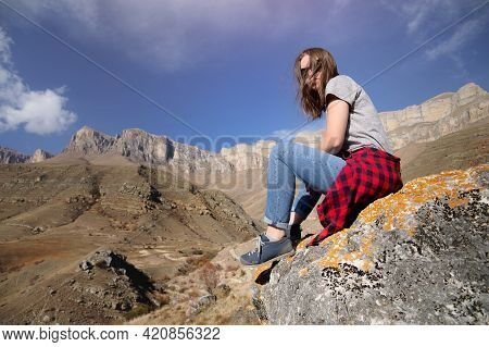 Happy Attractive Hipster Traveler Girl With Windy Hair And Smiling On A Background Of Sunny Mountain