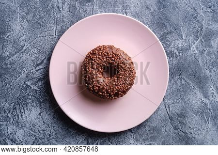 Chocolate Donut With Sprinkles On Pink Plate, Sweet Glazed Dessert Food On Concrete Textured Backgro