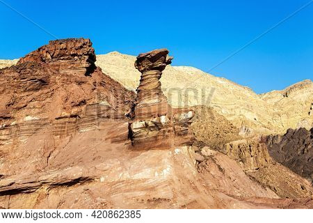 Bizarre forms of weathered sandstone in the mountains of Eilat. Eilat Mountains. The rocks are composed of sandstones, igneous and volcanic rocks. Multicolored landscape formations.