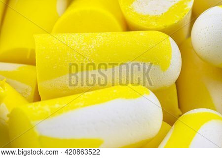 Macro Shots Of Multiple Earplugs In Yellow And White For Noise Protection.