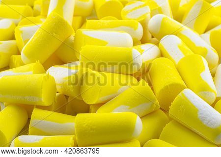 Background Made Of Macro Shots Of Multiple Earplugs In Yellow And White For Noise Protection.