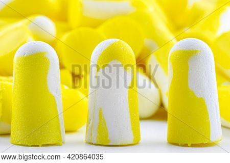 Macro Shot Of Three Yellow And White Earplugs For Noise Protection.