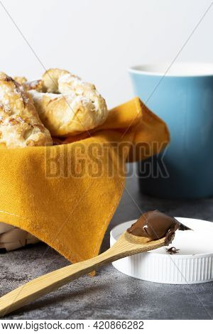 Spoon Full Of Chocolate Next To A Basket Of Puff Pastries And A Cup Of Coffee. Continental Breakfast