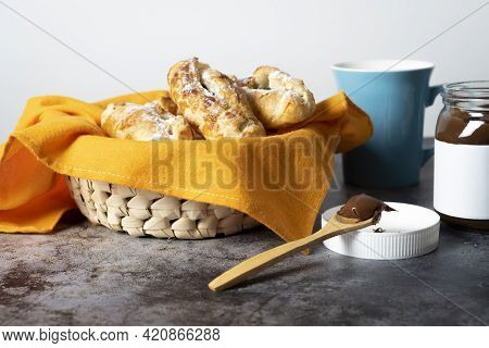 Spoon Full Of Chocolate Next To Basket Of Puff Pastries, Coffee Cup And Glass Jar Filled With Chocol