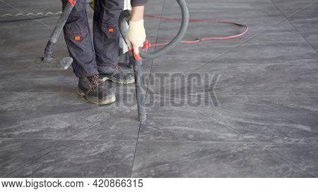 Worker Cleans Seams Between Tiles Using A Vacuum Cleaner. Tile Master, Vacuums The Floor To Prepare