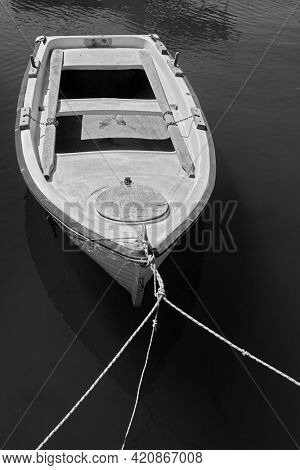 Moored old wooden oar boat. Black and white photography